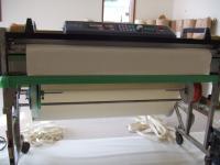 クロスをカットしてボンドをつける機械の下左側に緑・右側にオレンジのテープ
